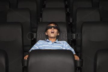 Preteen boy watching 3-D movie in theater