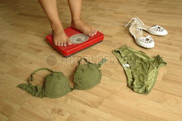 Unterwaesche und Schuhe neben einer Frau auf der Waage