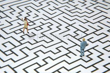 Mann und Frau durch Labyrinth voneinander getrennt
