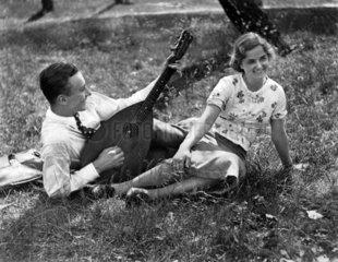 Mann spielt seiner Liebsten auf Laute vor