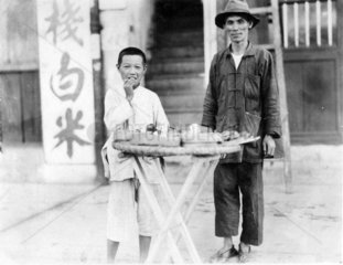 Bankok  Strassenhaendler Mann und Junge