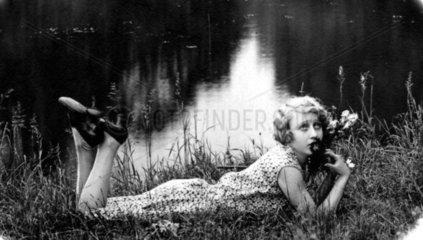 Frau liegt im Gras  1920