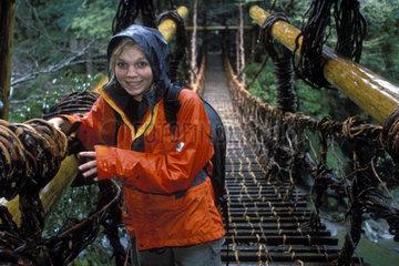 Frau ueberquert Haengebruecke bei Regen