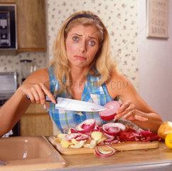 Frau weihnt beim Schneiden von Zwiebeln