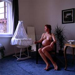 schwangere Frau sitzt nackt neben einer Wiege