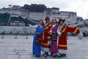 chinesische Touristinnen in tibetischen Kostuemen vor dem Potala Palast