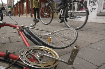 kaputtes Fahrrad und vorbeifahrender Radfahrer auf einem Buergersteig