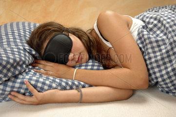 Frau mit Schlafmaske liegt im Bett