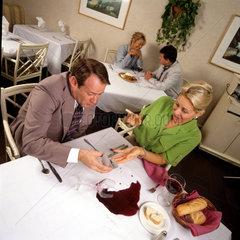 Mann kippt Weinglas um beim Heiratsantrag