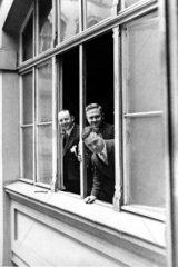 Drei Maenner schauen aus Fenster