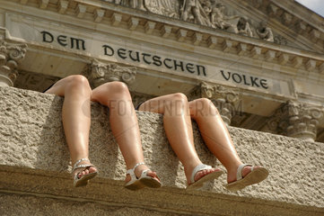 zwei Beinpaare vor der Reichstagsinschrift Dem deutschen Volke