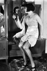 Frau in Unterwaesche mit Spiegel