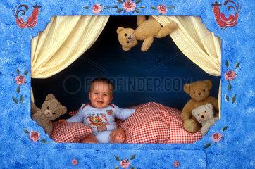 Baby mit Teddybaeren im Bett