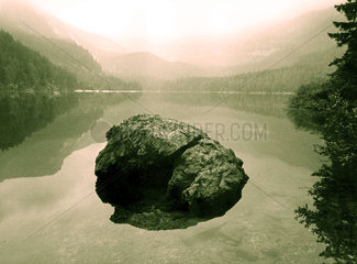 Italien - Trentino - Lago di Tovel - grosser Stein liegt in klarem Bergsee
