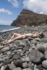 Frau sonnt sich an steinigem Strand