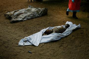 Einer von zahlreichen freiwilligen Helfern laeuft an den Leichen der Opfer der Tsunami Katastrophe entlang.
