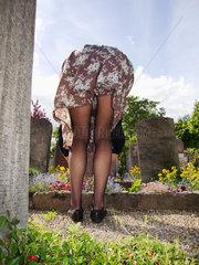 Frau bueckt sich ueber eine Grab