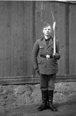 Mann in Uniform mit Spaten angetreten