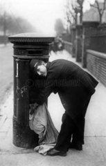 Postmann leert Briefkasten
