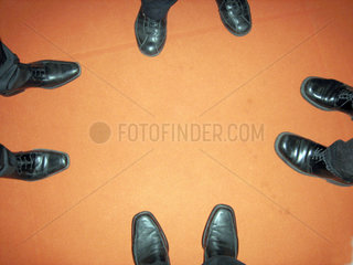 vier Paar Herrenschuhe auf orangefarbenem Teppich
