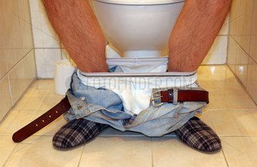 Mann sitzt auf der Toilette