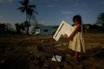 Ein Maedchen in den Ruinen eines von dem Tsunami zerstoerten Dorfes