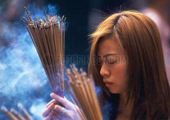 China - Hong Kong  Tempel  Frau mit Ruecherstaebchen