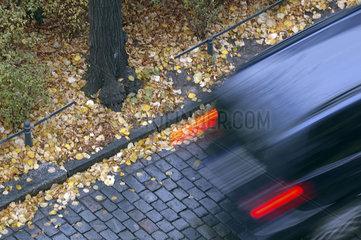 verschwommenes Auto faehrt auf Kopfsteinpflaster