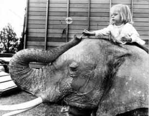 Kind sitzt auf Elefantenruecken