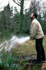 Mann imitiert Wasserlassen mit Schlauch