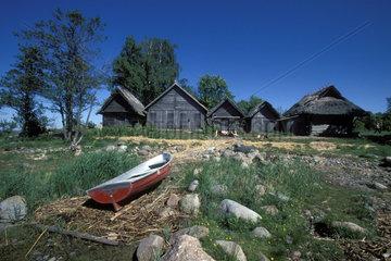 Ruderboot liegt vor Holzhuetten