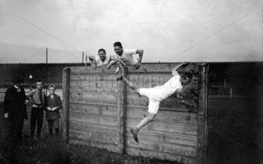 1930 - Maenner klettern ueber Holzbarriere