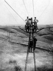 Maenner auf Telegrafenmast
