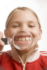 Maedchen zeigt mit Lupe ihre Zaehne