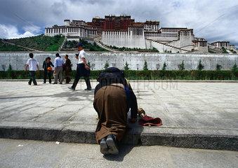 Tibet - Lhasa: Pilgerin kniet vor dem Potala Palast