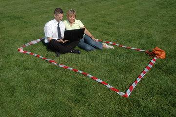 Geschaeftmann sitz mit Frau auf Wiese
