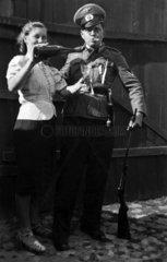 Frau mit Weinflasche und Mann in Uniform posieren vor der Kamera