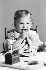 Kind isst Geburtstagstorte  erster Geburtstag