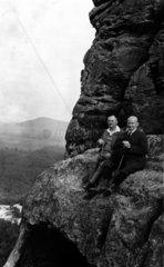 Zwei Maenner sitzen auf Felsen