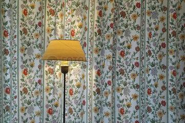 Stehlampe vor Uebergardine mit Blumenmuster
