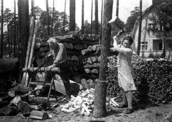 Mann und Frau beim Holzhacken und Saegen  1936