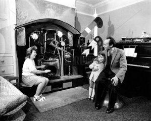 Mann Frau und Kind sitzen vor seltsamer Maschine