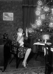 Frau zeigt Baby den Weihnachtsbaum