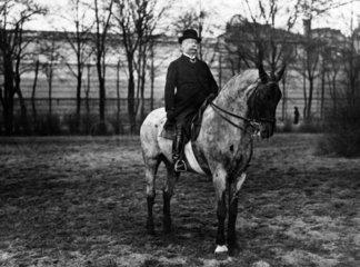 aelterer Mann reitet auf einem Pferd