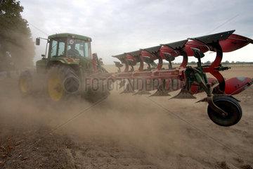 Ein Bauer pfluegt sein Feld