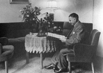 Mann liest am Wohnzimmertisch