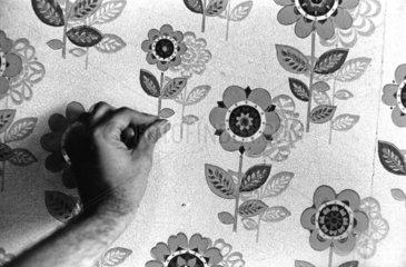 Hand auf Blumentapete