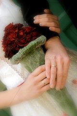 Hochzeit - Haende der Eheleute am Brautstrauss