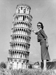 Frau stuetzt den Schiefen Turm zu Pisa