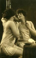 1910 schoene Frau kaemmt sich sinnlich vor Spiegel